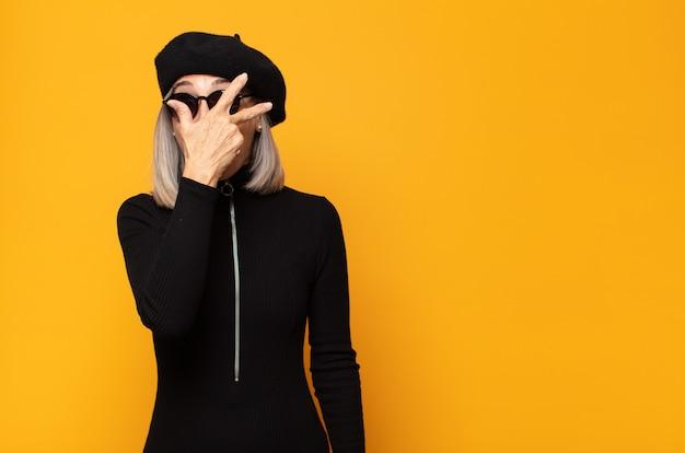 Vrouw van middelbare leeftijd die geschokt, bang of doodsbang kijkt, haar gezicht bedekt met de hand en tussen de vingers gluurt