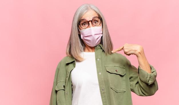 Vrouw van middelbare leeftijd die geschokt en verrast kijkt met wijd open mond, wijzend naar zichzelf