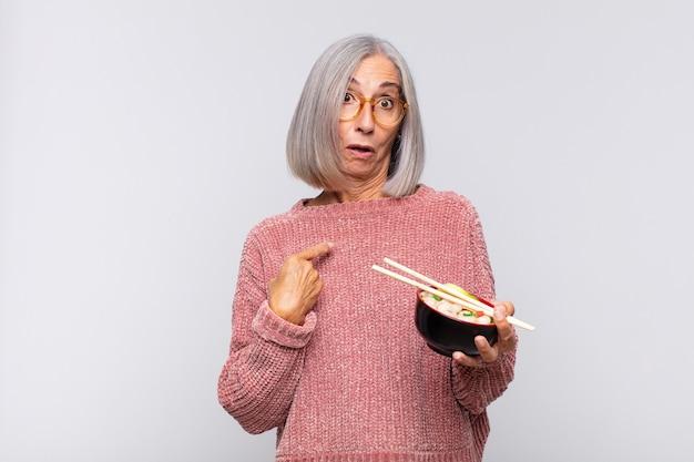 Vrouw van middelbare leeftijd die geschokt en verrast kijkt met wijd open mond