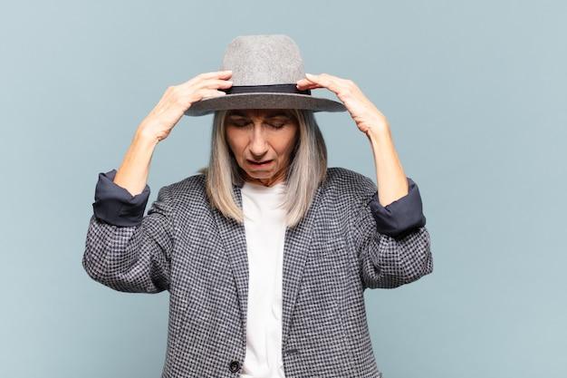 Vrouw van middelbare leeftijd die gestrest en gefrustreerd kijkt, onder druk werkt met hoofdpijn en last heeft van problemen