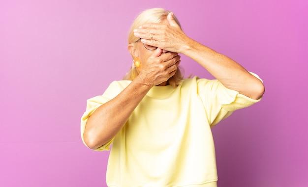 Vrouw van middelbare leeftijd die gezicht bedekt met beide handen en nee zegt tegen de camera! afbeeldingen weigeren of foto's verbieden