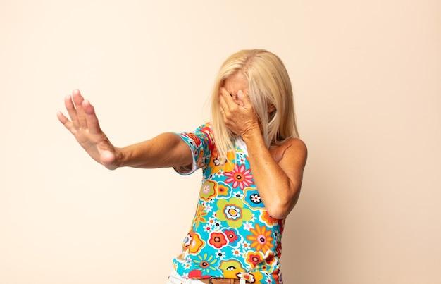 Vrouw van middelbare leeftijd die gezicht bedekt met hand en andere hand naar voren zet om de camera te stoppen, foto's of afbeeldingen weigeren