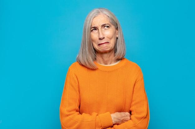 Vrouw van middelbare leeftijd die goofy en grappig kijkt met een dwaze schele uitdrukking, een grapje maakt en voor de gek houdt