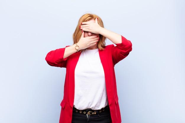 Vrouw van middelbare leeftijd die haar gezicht bedekt met beide handen en nee zegt tegen de camera! afbeeldingen weigeren of foto's verbieden