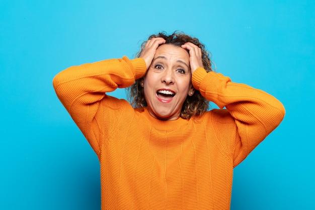 Vrouw van middelbare leeftijd die haar handen opheft, met open mond, zich buitengewoon gelukkig, verrast, opgewonden en gelukkig voelt