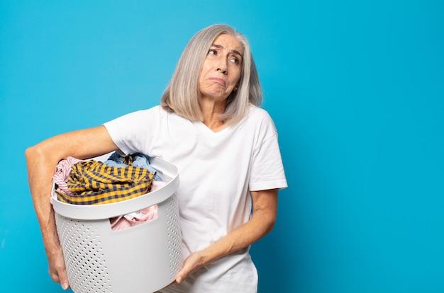 Vrouw van middelbare leeftijd die haar schouders ophaalt, zich verward en onzeker voelt, twijfelt met gekruiste armen en een verbaasde blik