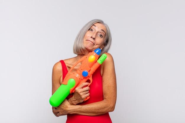 Vrouw van middelbare leeftijd die haar schouders ophaalt, zich verward en onzeker voelt, twijfelt met gekruiste armen en verbaasd kijkt met een waterpistool