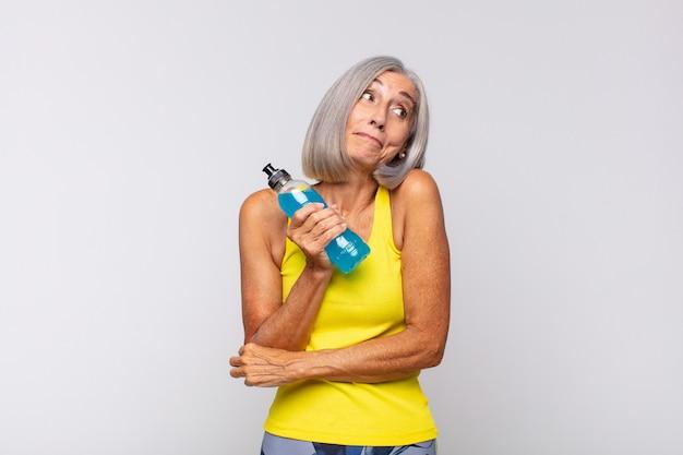 Vrouw van middelbare leeftijd die haar schouders ophaalt, zich verward en onzeker voelt, twijfelt met gekruiste armen en verbaasde blik. fitness concept