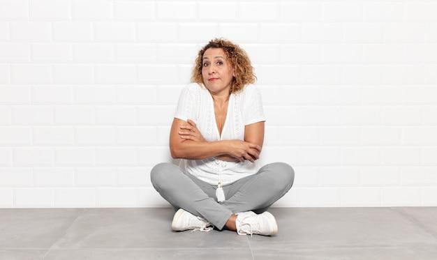 Vrouw van middelbare leeftijd die haar schouders ophaalt, zich verward en onzeker voelt, twijfelt met gekruiste armen en verbaasde blik