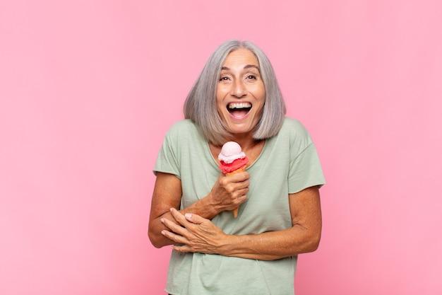 Vrouw van middelbare leeftijd die hardop lacht om een hilarische grap, zich gelukkig en opgewekt voelt, plezier heeft met een ijsje