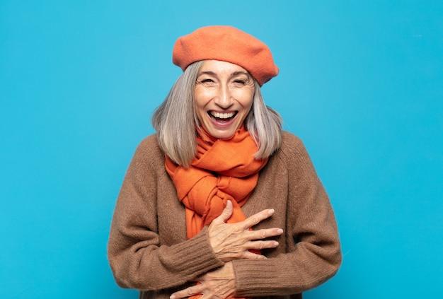 Vrouw van middelbare leeftijd die hardop lacht om een hilarische grap