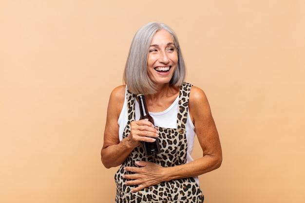 Vrouw van middelbare leeftijd die hardop lacht om een of andere hilarische grap, zich gelukkig en opgewekt voelt, lol heeft met een biertje