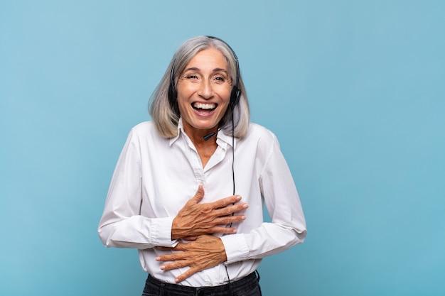 Vrouw van middelbare leeftijd die hardop lacht om een of andere hilarische grap, zich gelukkig en opgewekt voelt, lol heeft. telemarketeer concept
