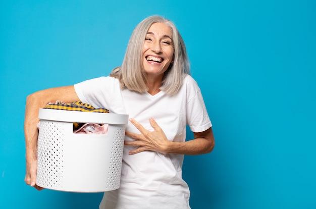 Vrouw van middelbare leeftijd die hardop lacht om een of andere hilarische grap, zich gelukkig en opgewekt voelt, plezier heeft