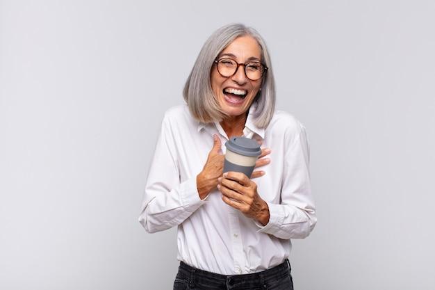 Vrouw van middelbare leeftijd die hardop lacht om een of andere hilarische grap