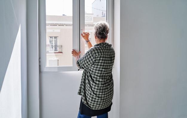 Vrouw van middelbare leeftijd die het raam in een kamer thuis sluit