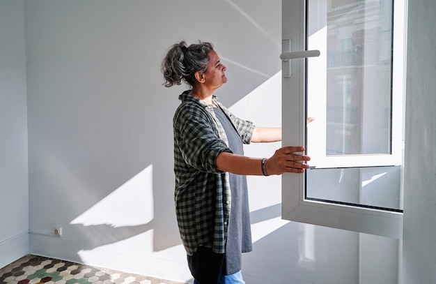 Vrouw van middelbare leeftijd die het raam opent in een kamer met gekleurde hydraulische vloeren