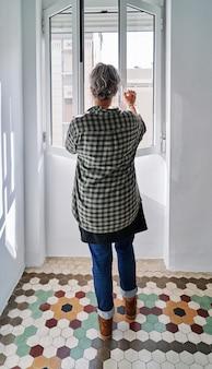 Vrouw van middelbare leeftijd die het raam sluit in een kamer met gekleurde hydraulische vloeren