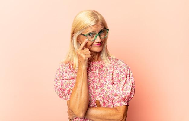 Vrouw van middelbare leeftijd die je in de gaten houdt, niet vertrouwt, kijkt en alert en waakzaam blijft