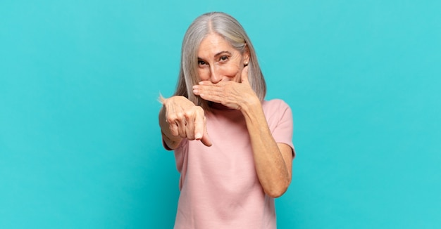 Vrouw van middelbare leeftijd die je uitlacht, naar de camera wijst en je belachelijk maakt of bespot