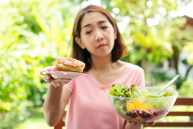 Vrouw van middelbare leeftijd die kiest tussen donuts en salade met een wazige vegetatieachtergrond