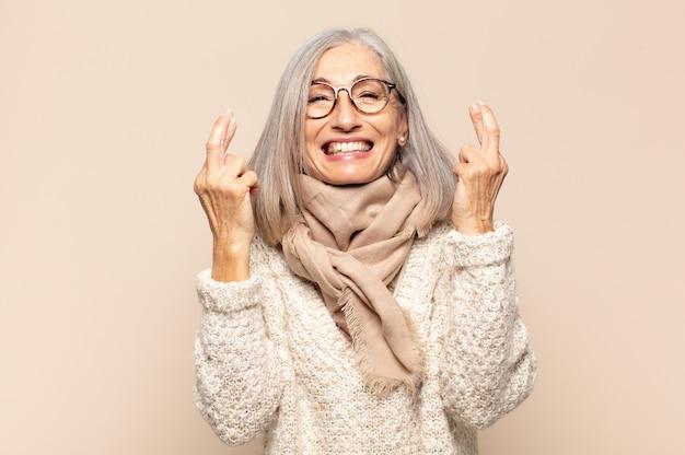 Vrouw van middelbare leeftijd die lacht en angstig beide vingers kruist, zich zorgen maakt en geluk wenst of hoopt