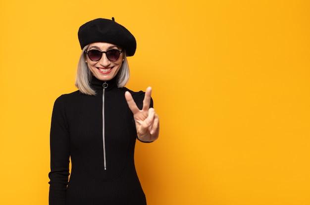Vrouw van middelbare leeftijd die lacht en er vriendelijk uitziet, met nummer twee of seconde met de hand naar voren