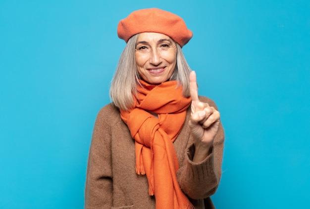 Vrouw van middelbare leeftijd die lacht en er vriendelijk uitziet, nummer één toont of eerst met de hand naar voren, aftellend