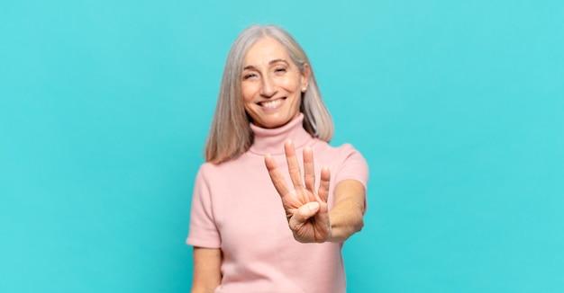 Vrouw van middelbare leeftijd die lacht en er vriendelijk uitziet, nummer vier of vierde toont met de hand naar voren, aftellend