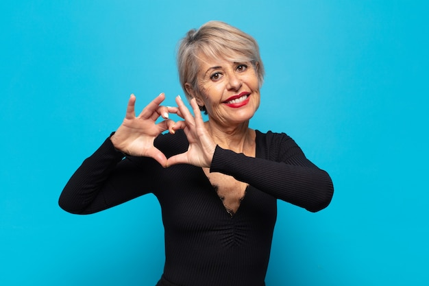 Vrouw van middelbare leeftijd die lacht en zich gelukkig, schattig, romantisch en verliefd voelt, hartvorm maakt met beide handen