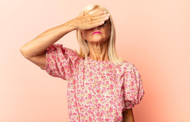 Vrouw van middelbare leeftijd die lacht en zich gelukkig voelt, de ogen bedekt met beide handen en wacht op een ongelooflijke verrassing