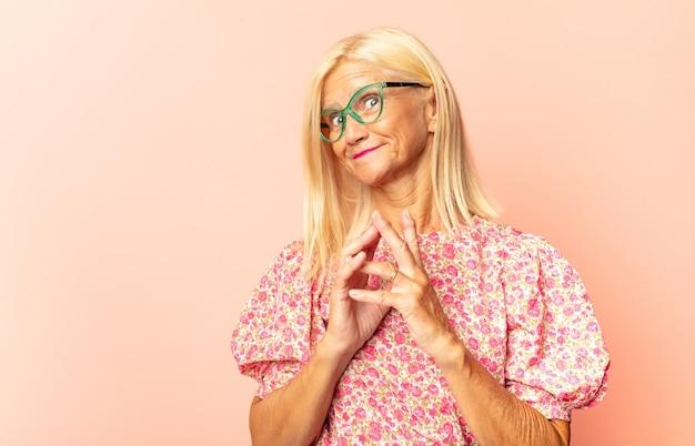 Vrouw van middelbare leeftijd die lacht, geniet van het leven, zich gelukkig, vriendelijk, tevreden en zorgeloos voelt met de hand op de kin