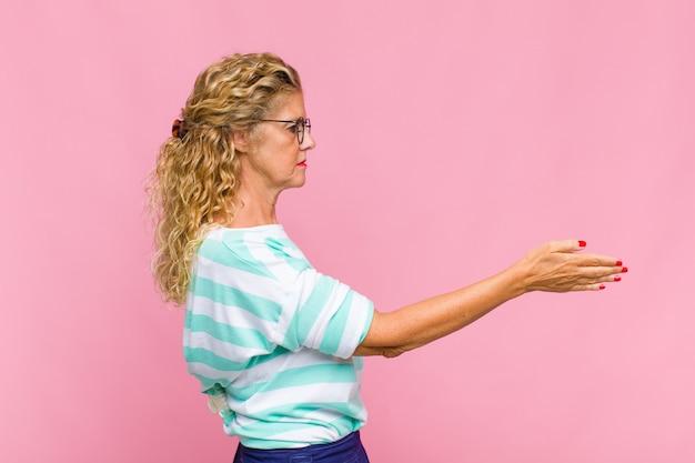 Vrouw van middelbare leeftijd die lacht, je begroet en een hand schudt om een succesvolle deal te sluiten
