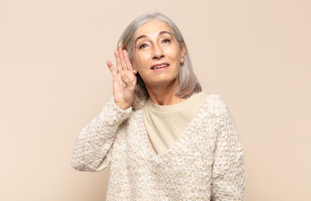 Vrouw van middelbare leeftijd die lacht, nieuwsgierig naar de zijkant kijkt, naar roddels probeert te luisteren of een geheim afluistert
