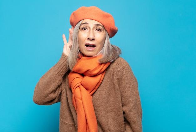 Vrouw van middelbare leeftijd die lacht, nieuwsgierig naar de zijkant kijkt, probeert te roddelen of een geheim afluistert