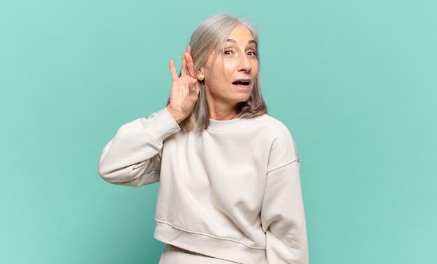 Vrouw van middelbare leeftijd die lacht, nieuwsgierig opzij kijkt, probeert te luisteren naar roddels of een geheim afluistert