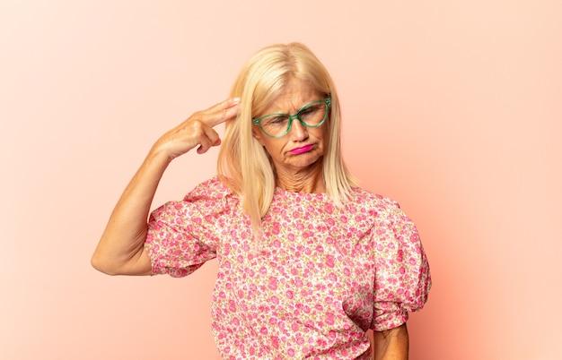 Vrouw van middelbare leeftijd die luid en boos schreeuwt om ruimte aan de zijkant te kopiëren, met de hand naast de mond