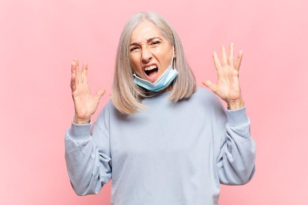 Vrouw van middelbare leeftijd die met handen in de lucht schreeuwt, zich woedend, gefrustreerd, gestrest en boos voelt
