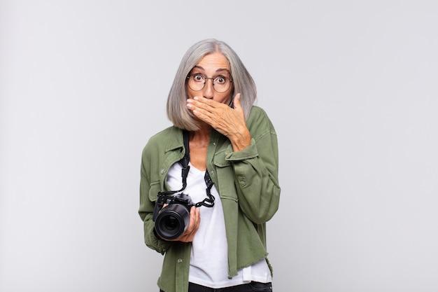 Vrouw van middelbare leeftijd die mond bedekt met handen met een geschokte, verbaasde uitdrukking, een geheim bewaren of oeps zeggen. fotograaf concept