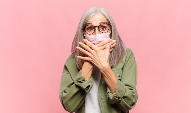 Vrouw van middelbare leeftijd die mond bedekt met handen met een geschokte, verbaasde uitdrukking, een geheim bewaren of oeps zeggen