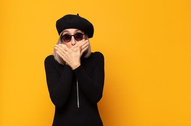 Vrouw van middelbare leeftijd die mond bedekt met handen met een geschokte, verbaasde uitdrukking
