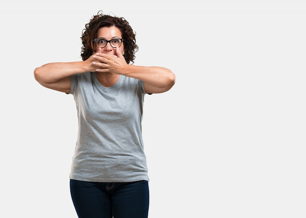 Vrouw van middelbare leeftijd die mond, symbool van stilte en onderdrukking, probeert om niets te zeggen