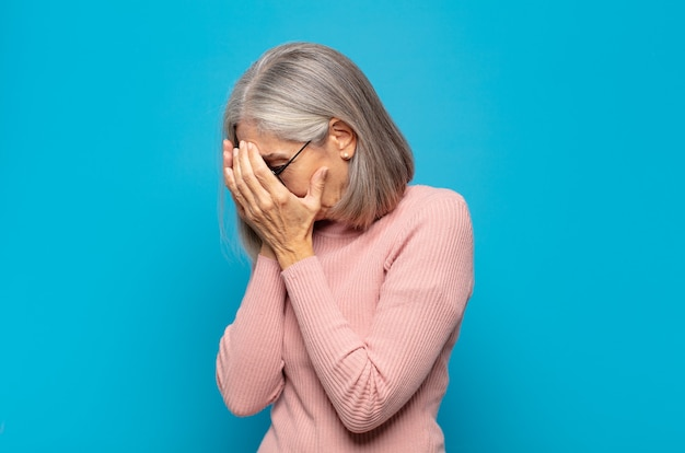 Vrouw van middelbare leeftijd die ogen bedekt met handen met een droevige, gefrustreerde blik van wanhoop, huilen, zijaanzicht
