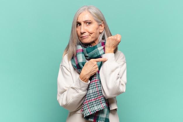 Vrouw van middelbare leeftijd die ongeduldig en boos kijkt, op horloge wijst, om stiptheid vraagt, wil op tijd zijn
