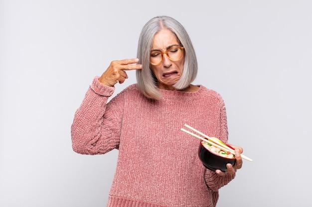 Vrouw van middelbare leeftijd die ongelukkig en gestrest kijkt, zelfmoordgebaar maakt pistoolteken met hand, wijzend naar hoofd aziatisch eten concept