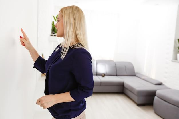 Vrouw van middelbare leeftijd die op de knop van de intercom drukt