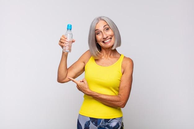 Vrouw van middelbare leeftijd die opgewonden en verrast kijkt en naar de zijkant en naar boven wijst om ruimte te kopiëren. fitnessconcept