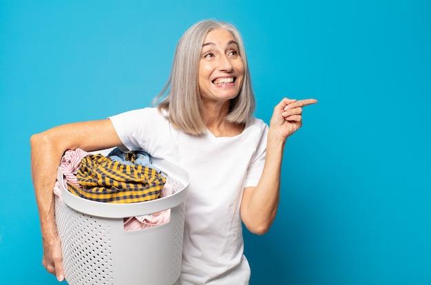 Vrouw van middelbare leeftijd die opgewonden en verrast kijkt en naar de zijkant en naar boven wijst om ruimte te kopiëren