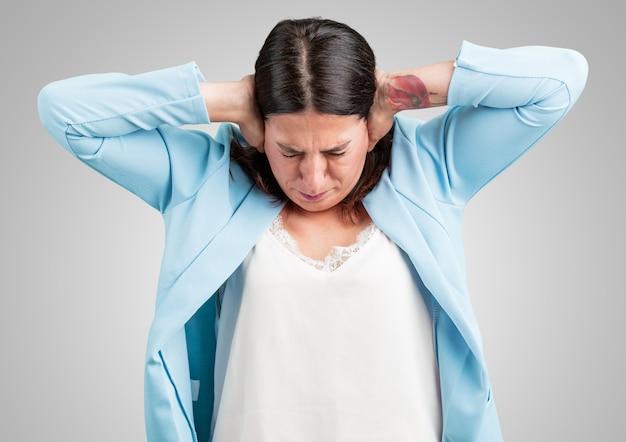 Vrouw van middelbare leeftijd die oren met handen, boos en moe van het horen van wat geluid