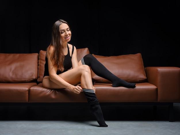 Vrouw van middelbare leeftijd die overknee warme sokken aantrekt